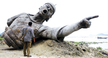 Obey my orders: An Indian bystander looks at a part of a bronze statue of Lachit Borphukan, which was to be installed in the middle of the river Brahmaputra, on Friday. Lachit Borphukan was a commander in the Ahom kingdom known for his leadership in the 1