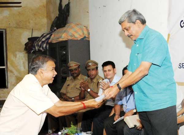 Chief Minister Manohar Parrikar handing over a cheque of financial assistance to a flood affected person at a function held at Mala, Panjim.