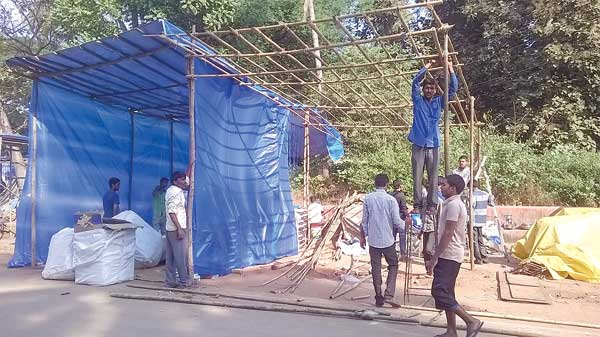 Workers complete the work of installing a stall near the Gandhi Circle at Old Goa on Monday.