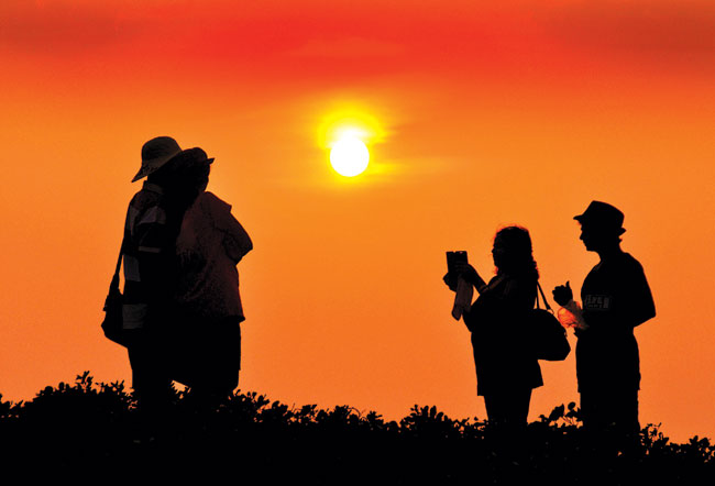 Sunset  boulevard: A tourist family is silhoutted against the setting sun as they click a photo at Miramar beach.   Photo by: Vincent Braganza